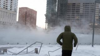 Imagem mostra homem de costas, em meio a prédios e ao chão coberto de neve em Chicago