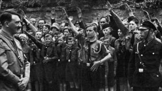 Adolf Hitler surveys young Nazi recruits.