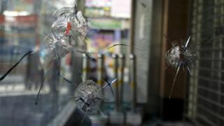 Bullet holes are pictured in the glass window of a Bank of China office located near the Dong Kuruk Bridge mosque in the city of Urumqi in China's Xinjiang Autonomous Region in this 11 July 2009 file image