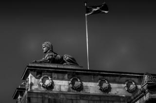 A statue on Princess street overlooking Edinburgh city, with the Scottish flag flying above