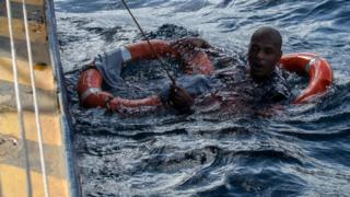 A migrant is rescued from the sea off Malta's coast,