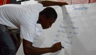 A volunteer writes down words in Palenquero on a whiteboard