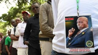 """A man wearing a badge with the photo of late former Kenya""""s President Daniel Arap Moi, queues to view his remains"""