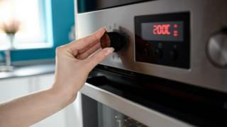 Woman turning oven on