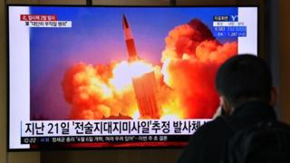 A man watches a news broadcast showing file footage of a North Korean missile test
