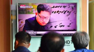 People watch a television news report, showing file footage of North Korean leader Kim Jong-Un, at a railway station in Seoul