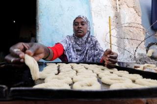 A Somali woman prepares traditional cakes and biscuits inside a bakery ahead of the upcoming Eid al-Fitr holiday, marking the end of the Muslim holy month of Ramadan, in Mogadishu, Somalia June 13, 2018