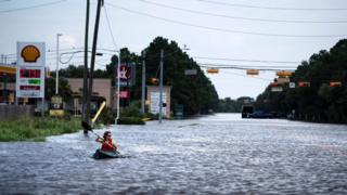 A woman paddles down a flooded road while shuttling deliveries for her neighbors during the aftermath of Hurricane Harvey on August 30, 2017 in Houston, Texas