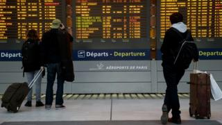 People watching departure boards at Paris Charles de Gaulle airport