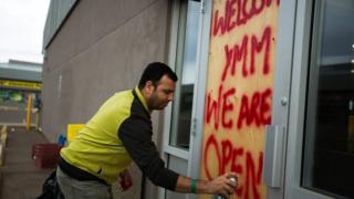 Convenience store manager Sunny Katoch paints a welcome sign on the back door as residents begin to flood back into their city after being evacuated due to raging wildfires in Fort McMurray, Alberta, Canada, 1 June 2016.