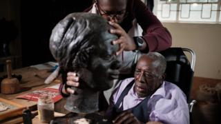 """Kenyan sculptor Edward Njenga (R), born in 1922, repairs his stoneware work """"Women""""s Guild Member (2008)"""" with the assistance of his grandson Edward Njenga who has same name at his at his studio in Nairobi on March 12, 2018. Njenga is the one of East Africas prominent sculptors who has been capturing scenes from Kenya""""s daily life mainly in the form of miniature figures."""