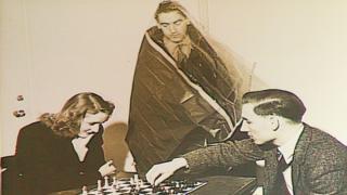 Voluntarios en el experimento jugando ajedrez mientras otro observa cubierto con una bolsa