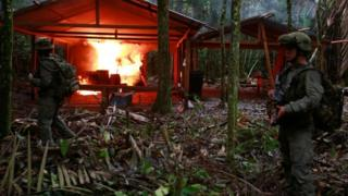 A Colombian anti-narcotics policeman stands guard after burning a cocaine lab in Calamar in Guaviare state, Colombia, August 2016.