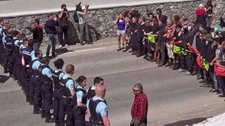 French gendarmes stand guard as demonstrators take part in a protest walk to help nearly 30 migrants to cross the Italian border to France at Montgenevre on April 22, during a weekend marked by action led by pro and anti-migrant groups. [Still image taken from Local Team video]