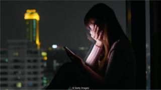 Mulher olha celular assustada