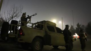 Security forces, including one soldier operating a vehicle-mounted machine gun, take up position outside the hotel