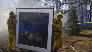 "Firefighters remove a painting as they continue to extinguish fires in a home during the ""Skirball Fire"""
