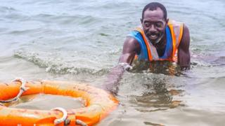 Lifeguard Nicholas Paul swimming with a lifebuoy in Lagos, Nigeria