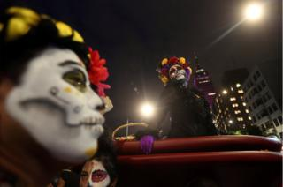 People with their faces painted to look like the popular Mexican figure called Catrina take part in a procession to celebrate the upcoming annual Day of the Dead at Juarez avenue, in Mexico City