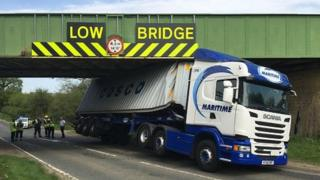 Lorry wedged under bridge