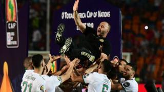 Algeria players carry dia coach shoulder high