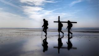 Pilgrims carry crosses along a beach to Holy Island