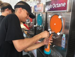 A man pours colourful frozen alcohol
