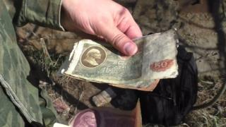 One of the Abandoned Country team holds Soviet-era banknotes