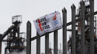 Union banner hanging from a fence in front of the Tata steelworks in the town of Port Talbot