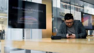 Cliente chino usando un iPhone en una tienda de Apple.