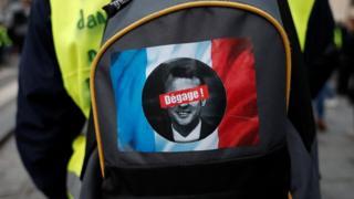 حقيبة متظاهر تحمل صورة ماكرون