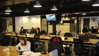 People work at tables inside of the 'WeWork' co-operative co-working space on March 13, 2013 in Washington, DC