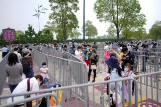 Visitors wearing face masks line up to enter the Shanghai Disneyland theme park