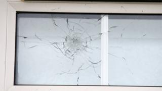Windows damaged from shots fired at house