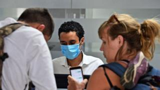 Airline employee with mask and two travellers.