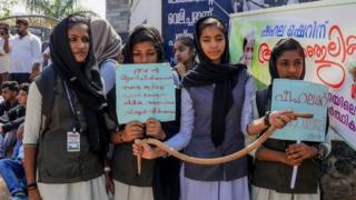 Students hold placards and a toy snake during a protest over the death of a girl after she was bitten by a snake inside her classroom at Sulthan Bathery