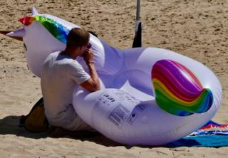 A man blows up an inflatable on a beach in Bournemouth