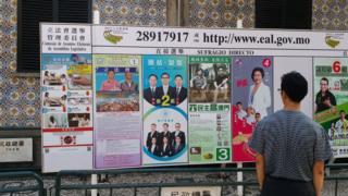 票站外张贴了各候选人宣传海报的看板