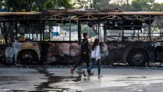 A burnt-out bus on the streets of Caracas after protests, photographed on 1 May 2019