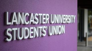 The Lancaster University Students' Union logo in white on a purple wall