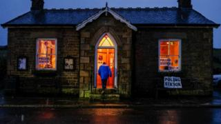 A man enters a polling station as snow falls in the North Pennines