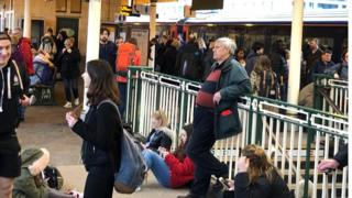 Passengers sit on the ground at Cardiff Central station as trains are delayed or cancelled