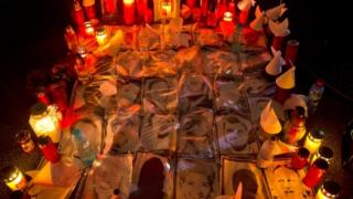 Candles are lit next to photographs of the victims outside the Colectiv nightclub in Bucharest, Romania. Photo: 6 November 2015