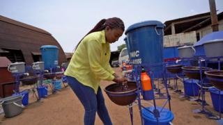 The BBC's Antonia Howard tests out a hands-free, foot-operated tap in Sierra Leone