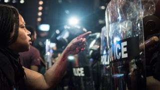 Protester faces riot police