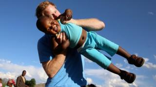 Prince Harry playing with a child in Lesotho