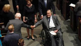 George H W Bush in a wheelchair, reaching for someone's hand, while on his way down a church aisle at his wife's funeral