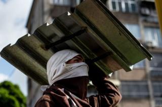 Un manifestante de oposición cubre su cabeza con un pedazo de lata en Caracas, Venezuela.