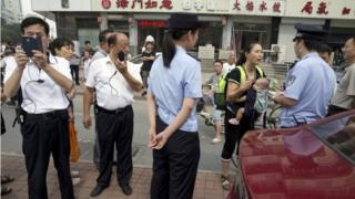Plain clothes police film journalists and talk to relatives outside the court in Tianjin (2 Aug 2016)