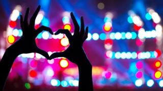 hands forming heartshape at gig